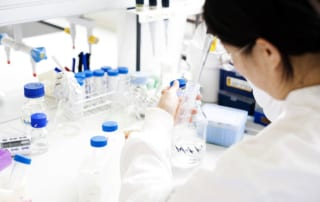 A woman in a lab using a pipette